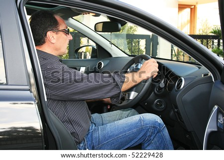 Man in new black car.