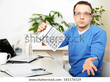 man in office, holding a calculator  - stock photo