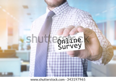 Man in office holding a card with a message text written on it Online survey - stock photo