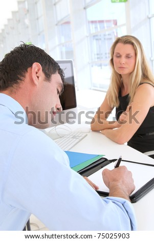 Man in office signing contract - stock photo