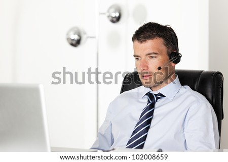 man in office with laptop and headset - stock photo
