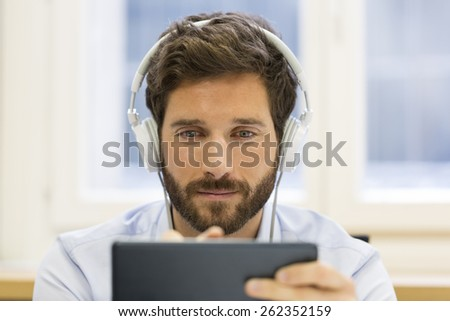 Man in office withe tablet pc and headphones - stock photo