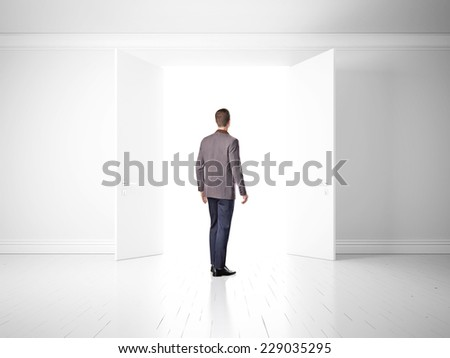 Man in open doors in white wall, way to success
