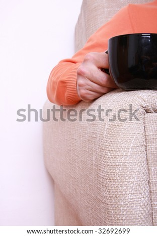 Man in orange blouse seating on the sofa and holding black cup.