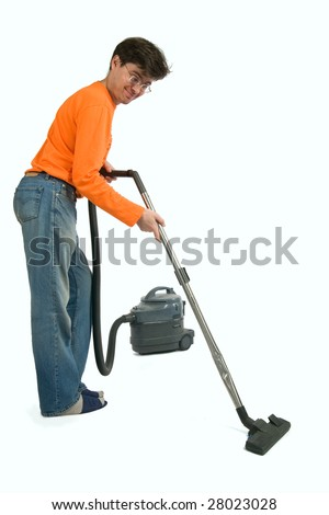 Man in orange sweater holds a old vacuum cleaner.