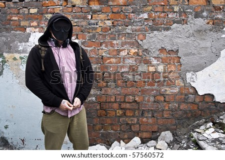 man in paintball mask near brick wall - stock photo
