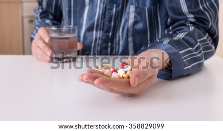 Man in pajamas sitting at white table and holding pile of pills in his palm and glass of water in other hand - stock photo