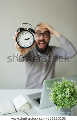 Man in panic with beard and glasses holds alarm clock and head scared of deadline - stock photo
