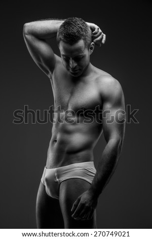 Man in panties looking down and posing on grey backround - stock photo