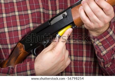 man in plaid shirt loading a semiautomatic shotgun - stock photo