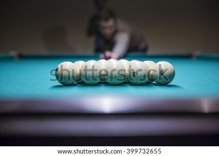 Man in  prepare for start game of billiard balls with triangle - stock photo