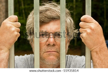 man in prison with hands wrapped around the bars - stock photo