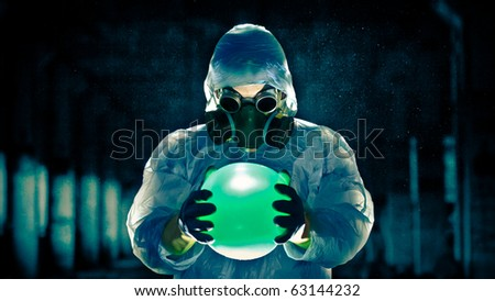 man in protective costume and respirator holding danger ball - stock photo
