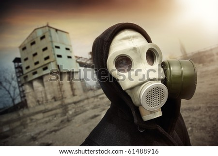 Man in protective gas mask near the industrial plant during radioactive sunset. Artistic colors and grain added - stock photo