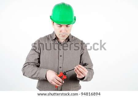 Man in protective helmet cuts the electrical cord - stock photo