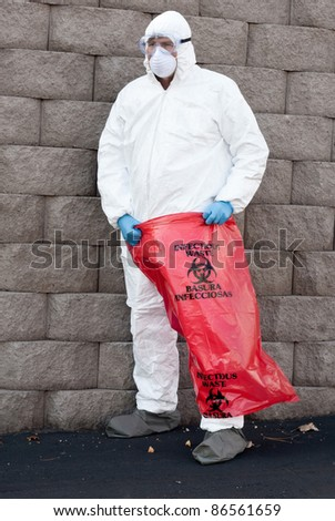 man in protective suit holding a hazardous waste bag