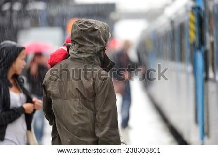 Man in raincoat in heavy rain on train station platform - stock photo