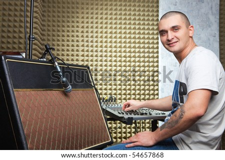 Man in recording studio sitting in front of mixer board. Guitar amplifier at foreground - stock photo