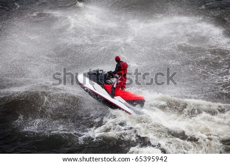 man in red life-jacket with jet on wave