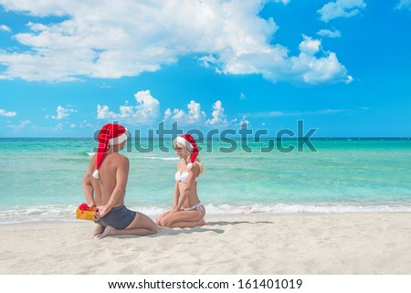 Man in red santa hat  giving a present to his blonde girlfriend on the sea beach - christmas vacations concept - stock photo