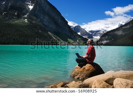 Man in red shirt on the lake shore - stock photo