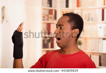 Man in red shirt staring at his own arm with shocked facial expression, wearing wrist brace support, blurry bookshelves background - stock photo