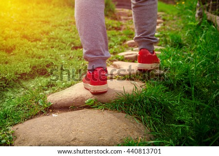 man in red sneakers standing on a stone path going up on the grass
