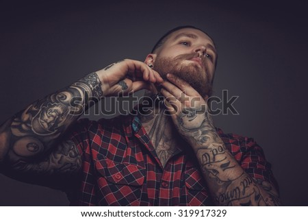 Man in red t shirt and tattooes on hands shaving his beard. - stock photo