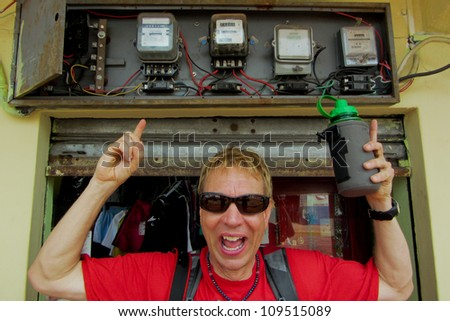 Man in red t-shirt looking surprised, pointing up at obsolete wiring on outside of building