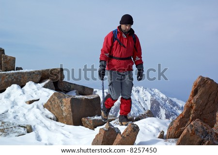 Man in red travels in winter mountain - stock photo