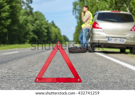 Man in reflective vest standing near broken car and calling to a car assistance. Focus on red triangle warning sign. - stock photo