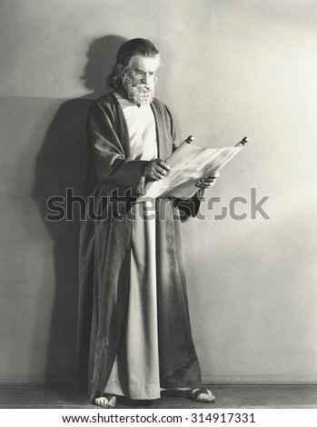 Man in robe reading scroll