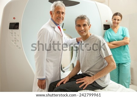 Man in 40s ready to undergo MRI scan, assisted by two smiling doctors.