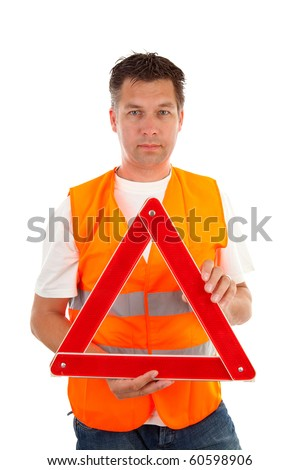 Man in safety vest holding foldaway reflective road hazard warning triangle over white background - stock photo