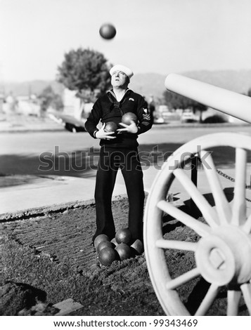 Man in sailors uniform trying to juggle cannon balls - stock photo