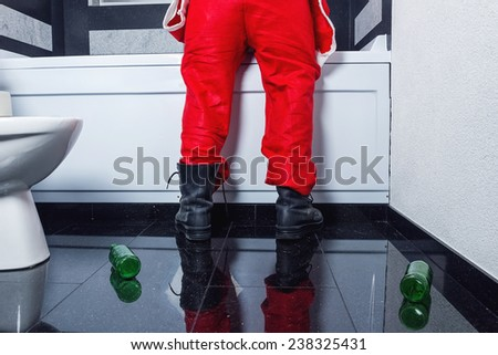 man in santa claus costume throwing up in the bathtub - stock photo