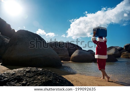 Man in Santa Claus costume walking along the beach with his Cooler on his head with copyspace - stock photo