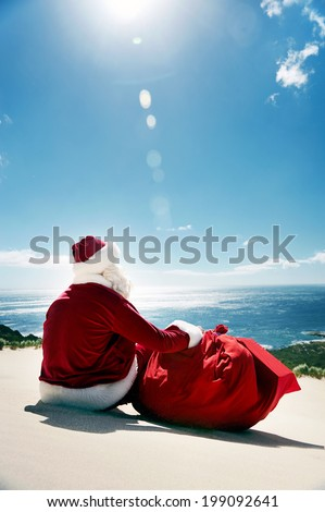Man in Santa costume sitting on a beach looking at view - stock photo
