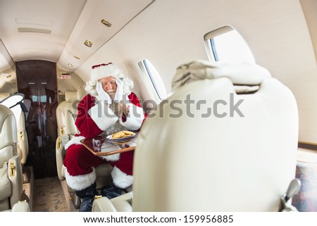 Man in Santa costume with head in hands sleeping in private jet