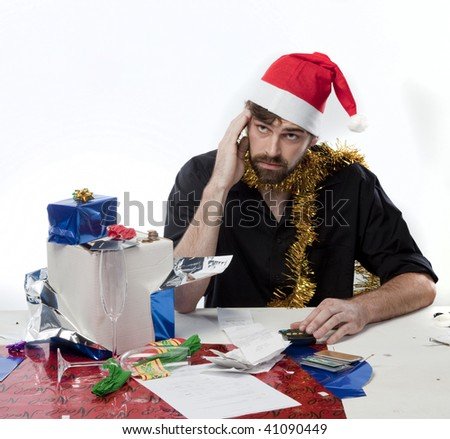 Man in Santa Hat depressed about Christmas spending - stock photo