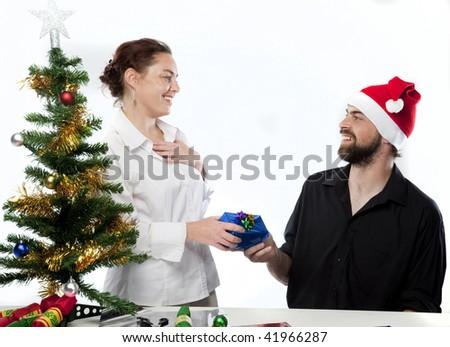 Man in Santa hat giving partner a gift - stock photo