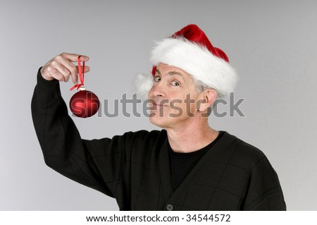 Man in Santa hat holding Christmas ornament