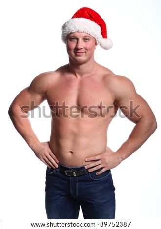 Man in Santa's red hat with strong body and muscles - stock photo