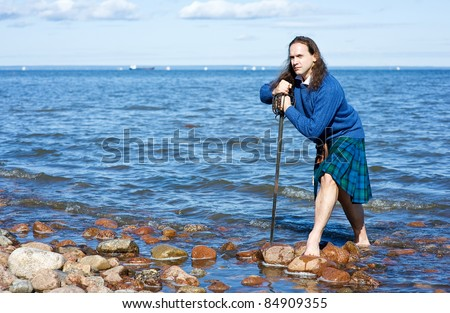 Man in Scottish costume in the water - stock photo
