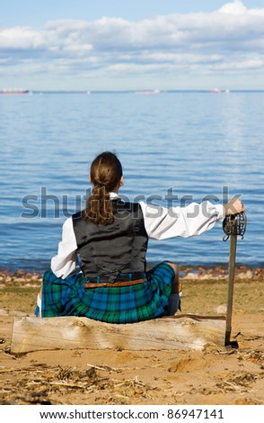 Man in scottish costume sitting on the stub and looking at the sea - stock photo