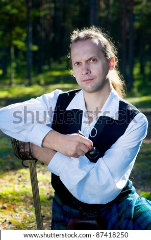 Man in scottish costume with sword and pipe outdoor - stock photo