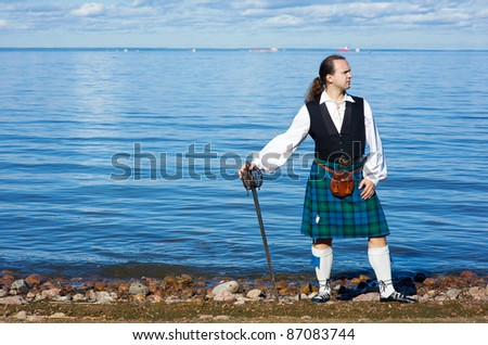 Man in scottish costume with sword looking at the sea - stock photo