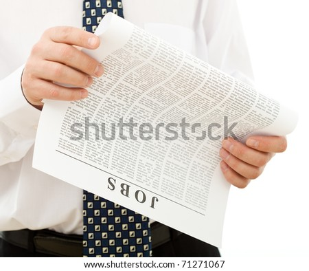 Man in shirt and tie looking for job reading a paper with classified ads - closeup, isolated
