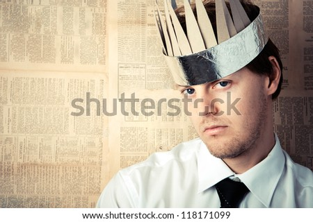 Man in shirt and tie with cardboard crown on head, image graded in vintage tone - stock photo
