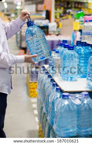 man in shirt choosing, selecting or buying a bottle of mineral drinking or distilling water at the shopping store focus on hands on the supermarket display shelf background - stock photo